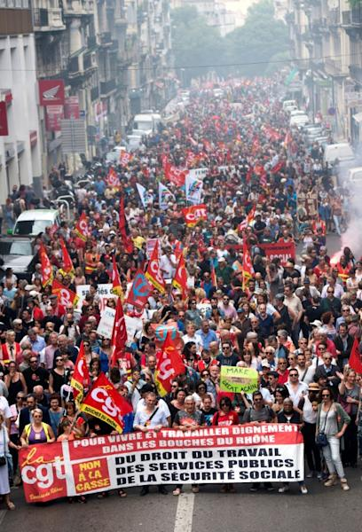 """Demonstrators hold a CGT trade union banner during a """"maree populaire"""" (working-class tide) demonstration to protest against French President's policy, on May 26, 2018 in Marseille, southern France"""