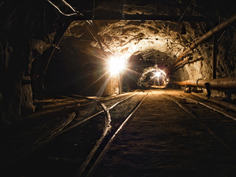 A tunnel in a coal mine with lights in the distance