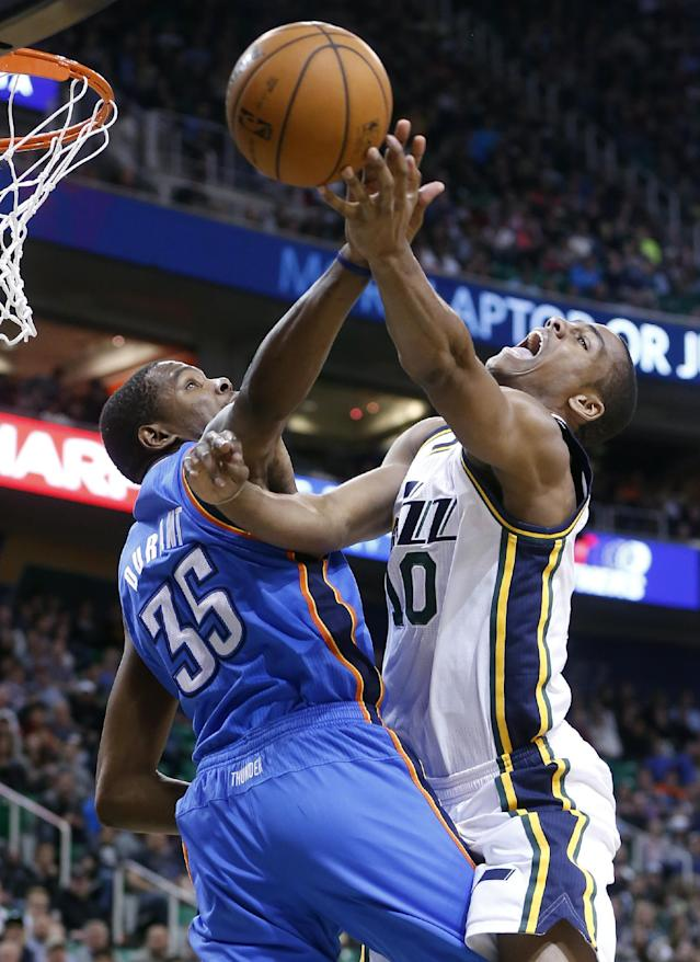 Utah Jazz guard Alec Burks (10) attempts a shot while Oklahoma City Thunder forward Kevin Durant (35) defends during the second half of an NBA basketball game in Salt Lake City, Tuesday, Jan. 7, 2014. The Jazz won 112-101. (AP Photo/Jim Urquhart)