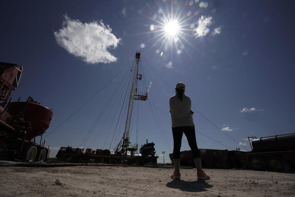 Ashley Williams Watt watches as a workover rig is used to help replug one of the abandoned wells at her ranch, Friday, July 9, 2021, near Crane, Texas. Some of her wells are leaking chemicals such as benzene, a known carcinogen, into fields and drinking water. (AP Photo/Eric Gay)