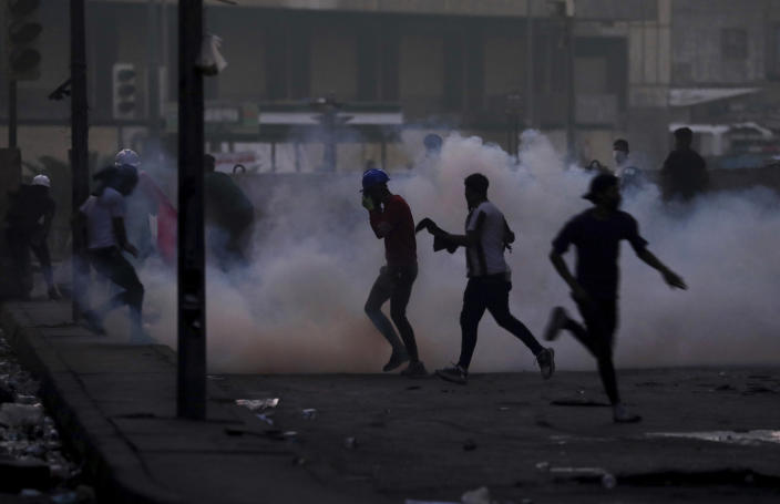Iraqi security forces fire tear gas to disperse anti-government protesters in central Baghdad, Iraq, Sunday, Nov. 10, 2019. (AP Photo/Hadi Mizban)