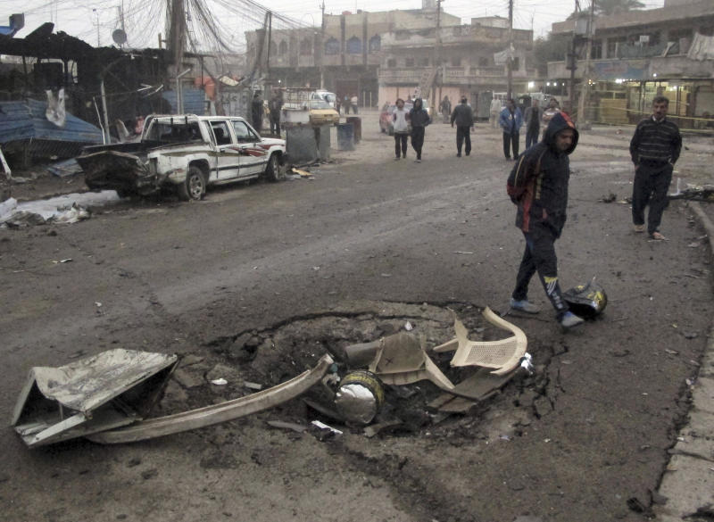 Iraqi civilians inspect a crater caused by a car bomb explosion at a commercial street in al-Ameen district in southeastern Baghdad, Iraq, Sunday, March 16, 2014. A series of car bomb attacks targeting commercial areas and a restaurant killed and wound scores of people, Saturday in Iraq's capital, Baghdad, authorities said. (AP Photo/Khalid Mohammed)