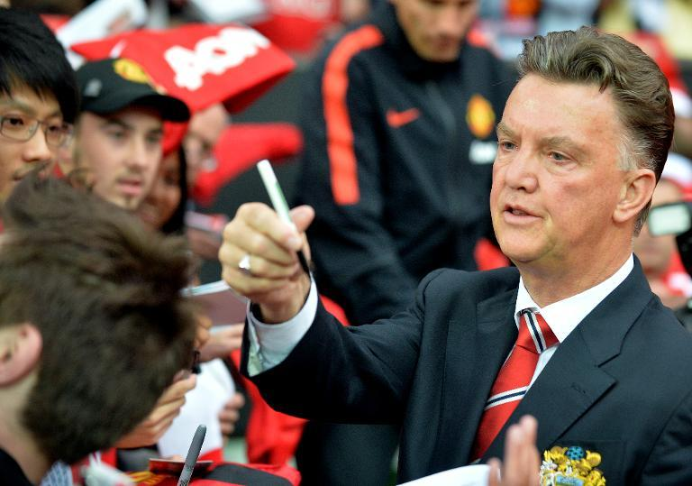 Manchester United's Dutch manager Louis Van Gaal signs autographs before a match in Manchester, England on August 12, 2014