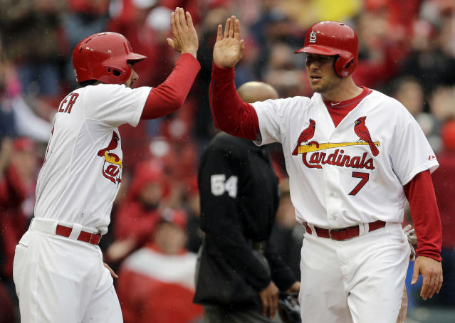 St. Louis Cardinals' Matt Holliday, right, is congratulated by teammate Matt Carpenter after scoring on a three-run double by Yadier Molina during the first inning of a baseball game against the Cincinnati Reds, Monday, April 7, 2014, in St. Louis. (AP Photo/Jeff Roberson)