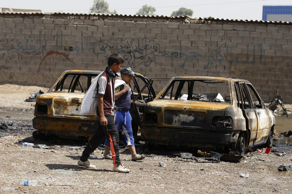 Children inspect the aftermath of a car bomb attack in Baghdad, Iraq, Thursday, Aug. 15, 2013. A wave of car bombs in the Iraqi capital on Wednesday killed and wounded dozens of people, the latest attacks in a months-long surge in violence. More than 3,000 people have been killed in violence during the past few months, raising fears Iraq could see a new round of widespread sectarian bloodshed similar to that which brought the country to the edge of civil war in 2006 and 2007. (AP Photo/Karim Kadim)