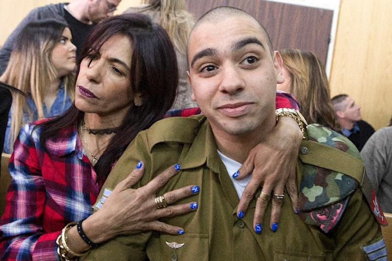 Israeli soldier Elor Azaria is embraced by his mother Oshra at the start of a hearing in a military court in Tel Aviv on February 21, 2017 at which he was sentenced to 18 months in prison for shooting dead a wounded Palestinian assailant (AFP Photo/JIM HOLLANDER)