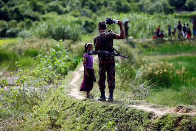 A member of Border Guard Bangladesh (BGB) tells a Rohingya girl not to come on Bangladesh side, in Cox's Bazar, Bangladesh