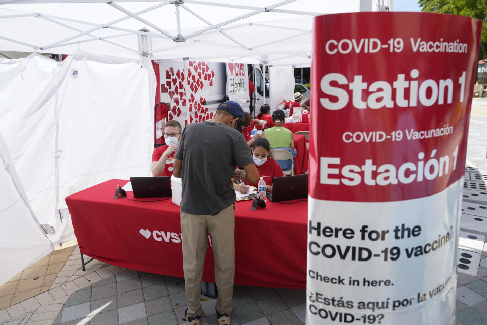 A man checks in to receive a vaccine at a pop-up vaccination site next to Maximo Gomez Park, also known as Domino Park, Monday, May 3, 2021, in the Little Havana neighborhood of Miami. (AP Photo/Wilfredo Lee)