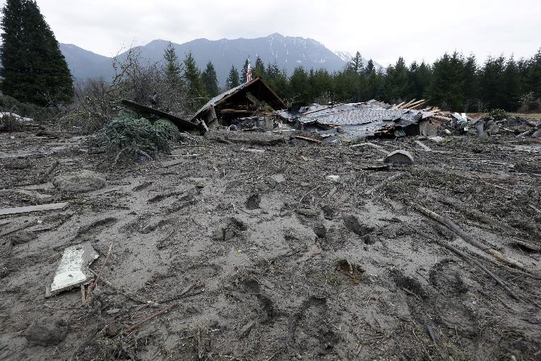 Footprints from searchers remain in mud at the edge of a deadly mudslide Tuesday, March 25, 2014, in Oso, Wash. At least 14 people were killed in the 1-square-mile slide that hit in a rural area about 55 miles northeast of Seattle on Saturday. Several people also were critically injured, and homes were destroyed. (AP Photo/Elaine Thompson)