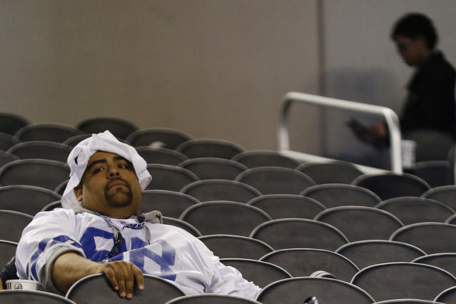 A Dallas Cowboys fan watches the field after a 23-22 loss to the Philadelphia Eagles at an NFL football game, Sunday, Dec. 29, 2013, in Arlington, Texas. (AP Photo/Tim Sharp)
