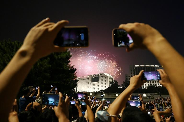 People gather to watch fireworks in the distance during an art performance being held at the Bird's Nest national stadium to mark the upcoming 100th anniversary of the founding of the Communist Party, in Beijing on June 28, 2021