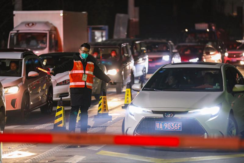 A government worker directs traffic at a toll gate in Wuhan in central China's Hubei province Tuesday, January 21, 2020.