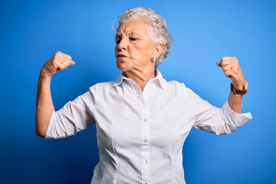 Senior beautiful woman wearing elegant shirt standing over isolated blue background showing arms muscles smiling proud. Fitness concept.