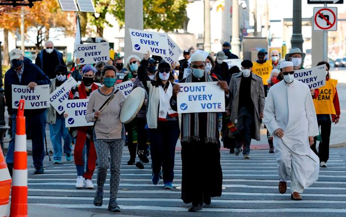 Protestors who want every vote counted from the 2020 presidential election, march down Woodward Avenue in Detroit - JEFF KOWALSKY/AFP