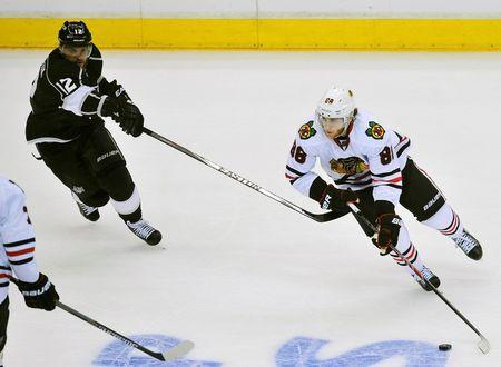 May 30, 2014; Los Angeles, CA, USA; Chicago Blackhawks right wing Patrick Kane (88) controls the puck against the defense of Los Angeles Kings right wing Marian Gaborik (12) during the third period in game six of the Western Conference Final of the 2014 Stanley Cup Playoffs at Staples Center. Mandatory Credit: Gary A. Vasquez-USA TODAY Sports