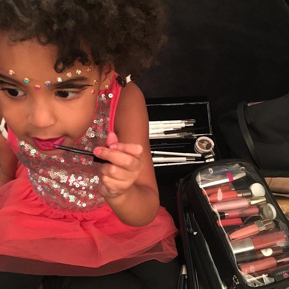 <p>Beyoncé posted a photo of Blue Ivy getting into her mom's impressive selection of lip colors and other makeup. Blue swipes on a bright magenta hue, which pairs nicely with the series of rhinestones across her forehead and the floating liner in her crease.</p>