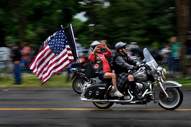 <p>A passenger on a motorcycle takes a photo as they and thousands of others made their way on Constitution Ave. today. Thousands of motorcyclists swarmed the Washington, D.C. area today to take part for the 30th annual Rolling Thunder Memorial Day event. (Photo: Michael S. Williamson/The Washington Post via Getty Images) </p>
