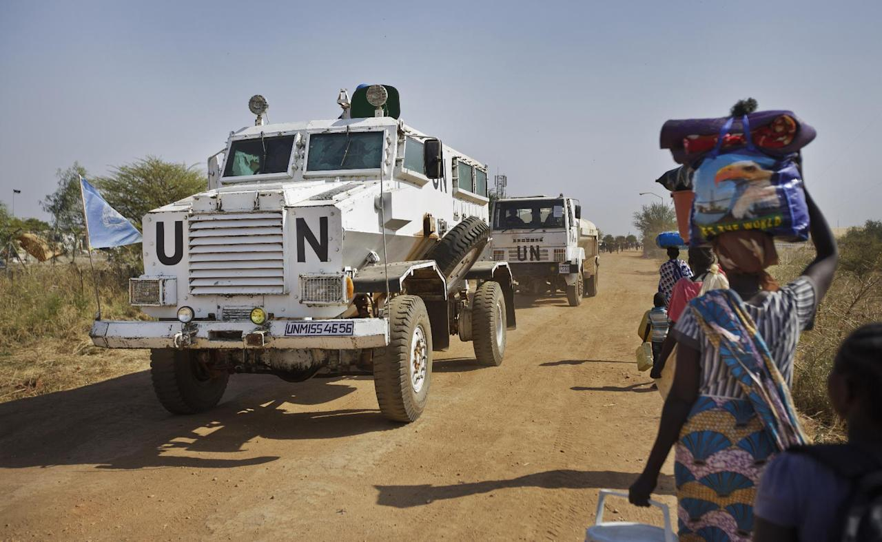 "FILE - In this Monday, Dec. 30, 2013 file photo, a United Nations armored vehicle passes displaced people walking towards the U.N. camp in Malakal, South Sudan. Minister of Cabinet Affairs Martin Lomuro said Saturday, Nov. 26, 2016, that the government has accepted to have with ""no conditions"" an increased peacekeeping force as mandated by the U.N. Security Council in August. (AP Photo/Ben Curtis, File)"