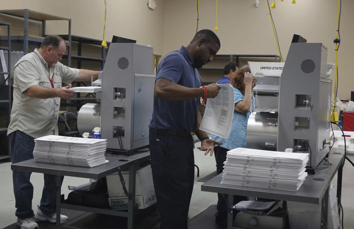 Election workers place ballots into electronic counting machines in Lauderhill, Fla., on Sunday. (Photo: Joe Cavaretta/South Florida Sun-Sentinel via AP)