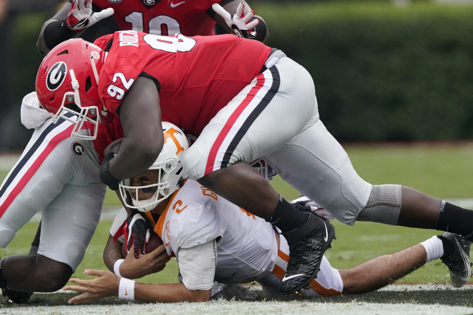 Tennessee quarterback Jarrett Guarantano (2) is brought down by Georgia defensive lineman Julian Rochester (92) after a short run in the first half of an NCAA college football game Saturday, Oct. 10, 2020, in Athens, Ga. (AP Photo/John Bazemore)