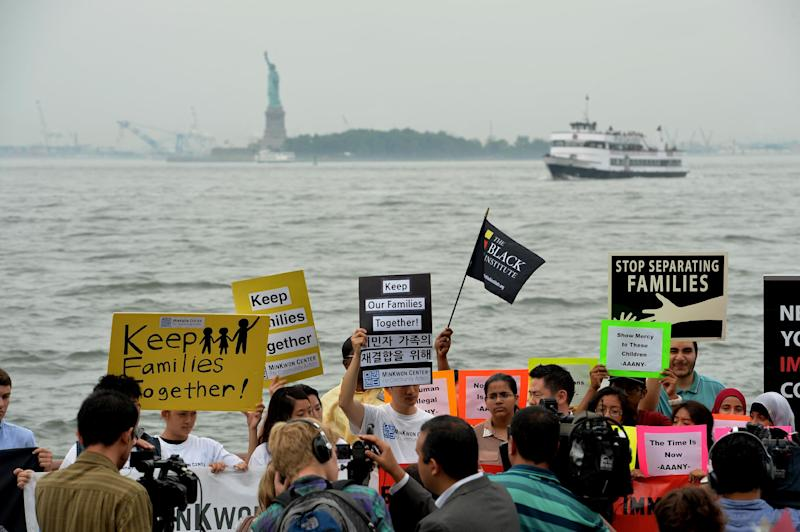 People protest for immigration reform at New York's Battery Park with the Statue of Liberty in the background July 14, 2014 (AFP Photo/Stan Honda)