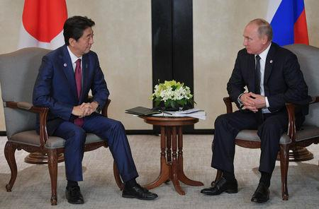 Japanese PM Abe and Russian President Putin attend a meeting on the sidelines of the ASEAN-Russia Summit in Singapore