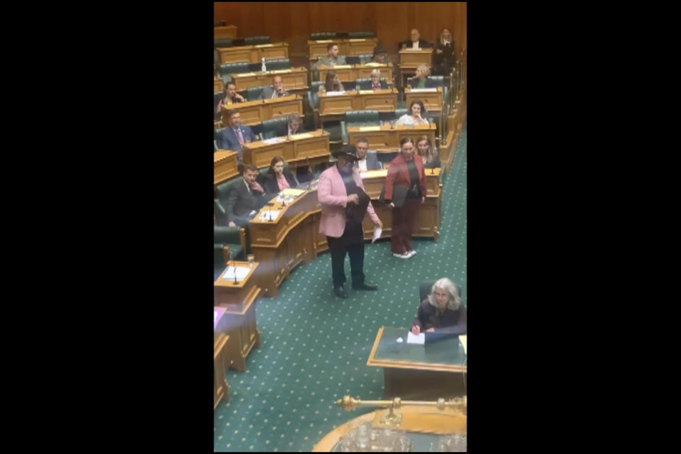 In this image from video, Indigenous New Zealand lawmaker Rawiri Waititi, center, performs a Maori haka in Parliament in Wellington, New Zealand, Wednesday, May 12, 2021. Waititi was thrown out of Parliament's debating chamber for performing a Maori haka in protest at what he said were racist arguments. Waititi's stance came after ongoing debate among lawmakers about the government's plans to set up a new Maori Health Authority as part of sweeping changes to the health care system. His party's other co-leader, Debbie Ngarewa-Packer is seen at right. (Thomas Coughlan via AP)
