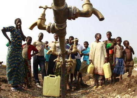 Congolese refugees, displaced by fighting between the Congo army and rebel group Allied Democratic Forces (ADF) last week, gather around dry water taps at Bukanga transit camp