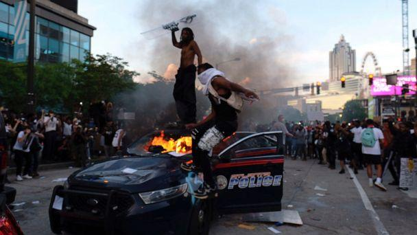 PHOTO: Protesters smash police cars in Atlanta, Friday, May 29, 2020. Protesters marched for George Floyd, who died after being restrained by Minneapolis police officers on Memorial Day. (Ben Gray/Atlanta Journal-Constitution via AP)