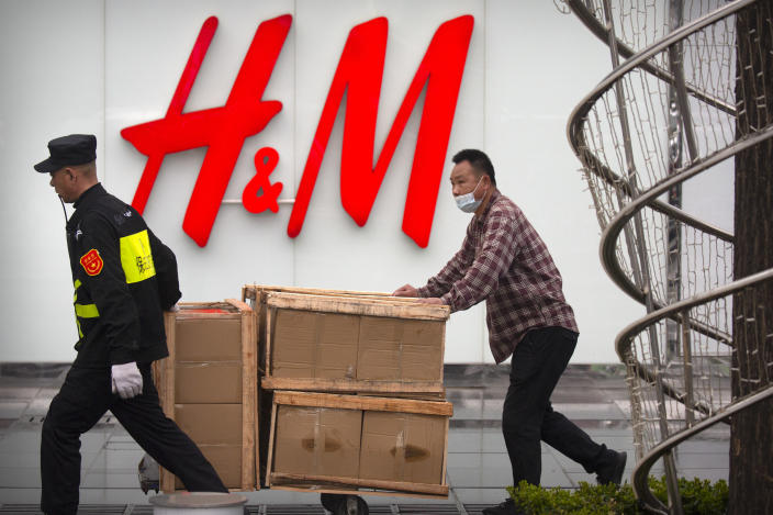 A security guard helps a worker move boxes past an H&M clothing store at a shopping mall in Beijing, Friday, March 26, 2021. H&M disappeared from the internet in China as the government raised pressure on shoe and clothing brands and announced sanctions Friday against British officials in a spiraling fight over complaints of abuses in the Xinjiang region.(AP Photo/Mark Schiefelbein)