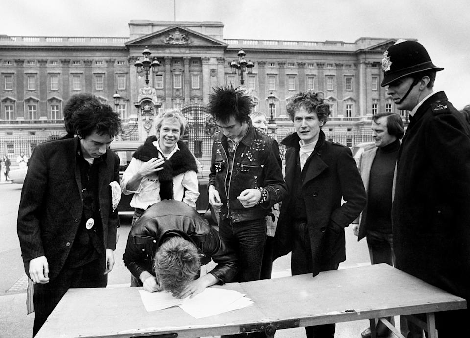 The group Sex Pistols, signing a new recording contract with A&M Records outside Buckingham Palace in London, (l/r) Johnny Rotten, Steve Jones, Paul Cook, bass player Sid Vicious and the group's manager Malcolm McLaren (Archive/PA) (PA Archive)