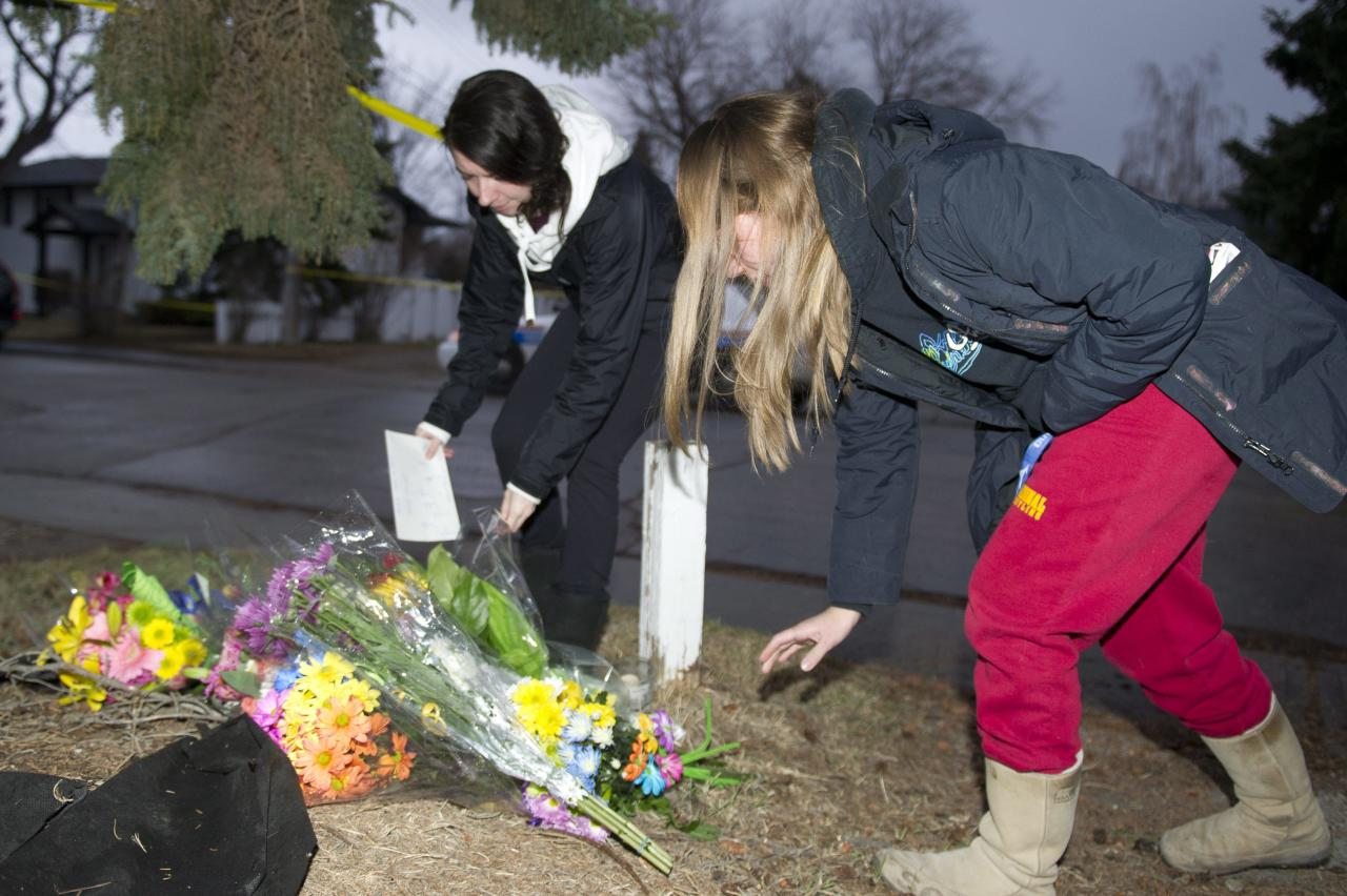 "Unidentified women leave flowers at the scene of the multiple fatal stabbing in northwest Calgary, Alberta on Tuesday, April 15, 2014. ""This is the worst murder _ mass murder _ in Calgary's history,"" police Chief Rick Hanson said at a news conference Tuesday. (AP Photo/The Canadian Press, Larry MacDougal)"