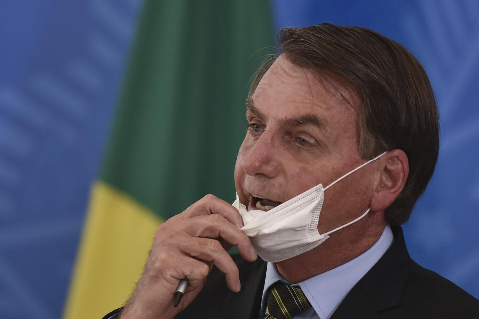 Brazil's President Jair Bolsonaro removes his mask to speak to journalists after a press conference on the new coronavirus, at the Planalto Presidential Palace in Brasilia, Brazil, Wednesday, March 18, 2019. For most people COVID-19 causes mild or moderate symptoms. For others, especially the elderly and people with existing health problems, it can cause many other serious illnesses, including pneumonia. (AP Photo/Andre Borges)