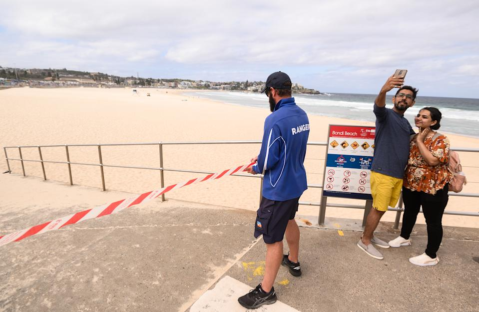 A ranger tapes off an entrance to Bondi Beach following its closure to the public on Sunday. Source: AAP