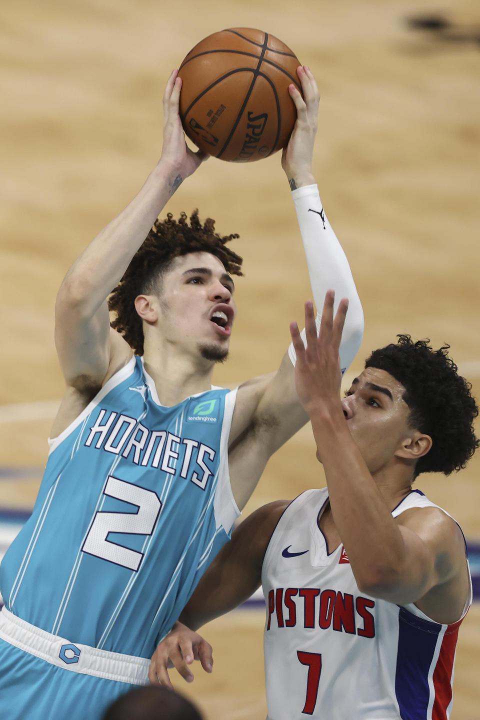 Charlotte Hornets guard LaMelo Ball, left, shoots against Detroit Pistons guard Killian Hayes in the second half of an NBA basketball game in Charlotte, N.C., Saturday, May 1, 2021. (AP Photo/Nell Redmond)