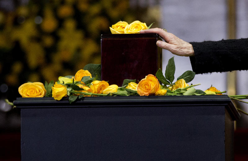 Silvia Lemus, widow of the Mexican author Carlos Fuentes, touches the urn containing Colombian Nobel Literature laureate Gabriel Garcia Marquez's ashes during an homage to the beloved author at the Palace of Fine Arts in Mexico City, Monday, April 21, 2014. The ashes of Garcia Marquez were taken Monday to Mexico City's majestic Palace of Fine Arts, where thousands of admiring readers began paying tribute to the Colombian Nobel laureate considered one of the greatest Spanish-language authors of all time. (AP Photo/Eduardo Verdugo)