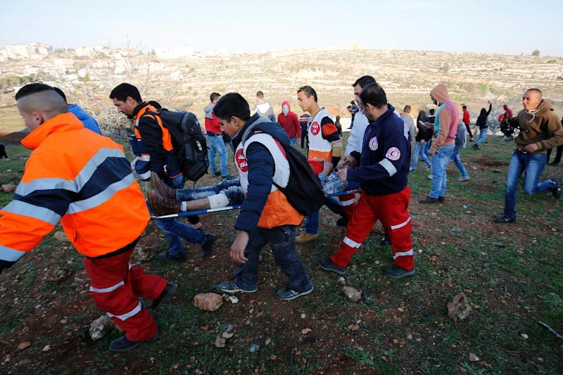 A Palestinian protester is evacuated by on a stretcher Palestinian Red Cresent members after being wounded during clashes with Israeli security forces near the Ofer Israeli military prison on December 25, 2015 (AFP Photo/Abbas Momani)