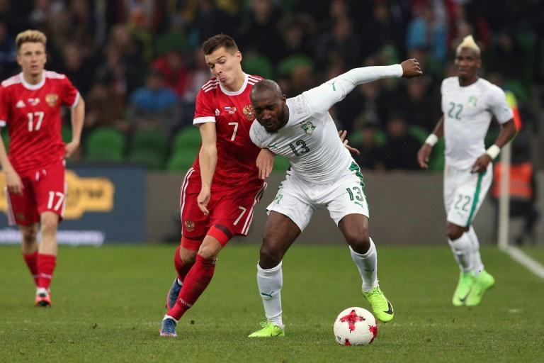 Russia's forward Dmitry Poloz and Ivory Coast's forward Giovanni Sio vie for the ball during their international friendly football match March 24, 2017
