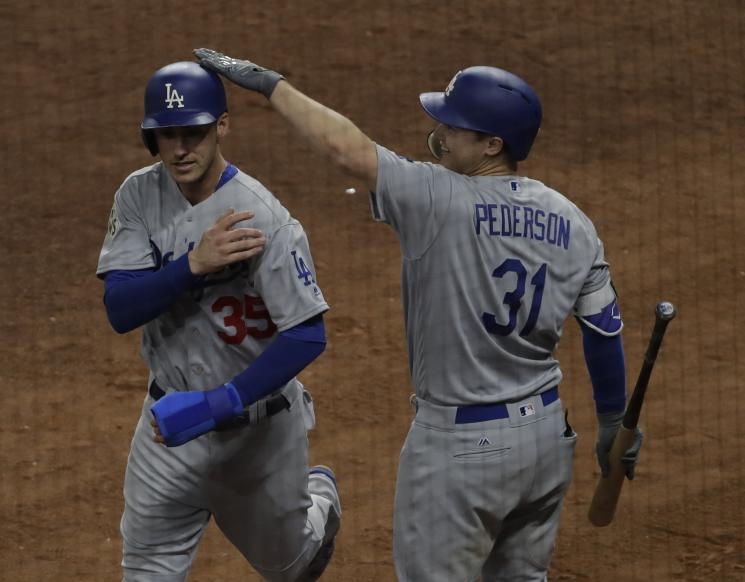 Dodgers' rookie Cody Bellinger is congratulated by Joc Pederson after scoring on a hit by Logan Forsythe during Game 4 of the World Series. (AP)