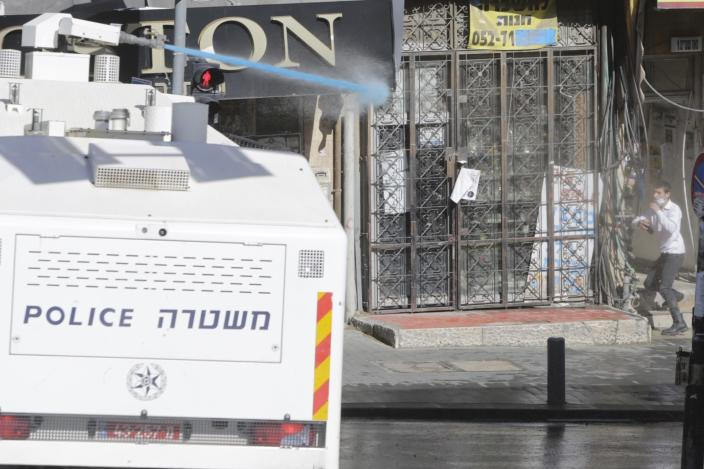Israeli police shoots a water canon in an ultra-orthodox neighborhood In Jerusalem, Sunday, Jan. 24, 2021. Ultra-Orthodox demonstrators clashed with Israeli police officers dispatched to close schools in Jerusalem and Ashdod that had opened in violation of health regulations on Sunday. (AP Photo/Sebastian Scheiner)