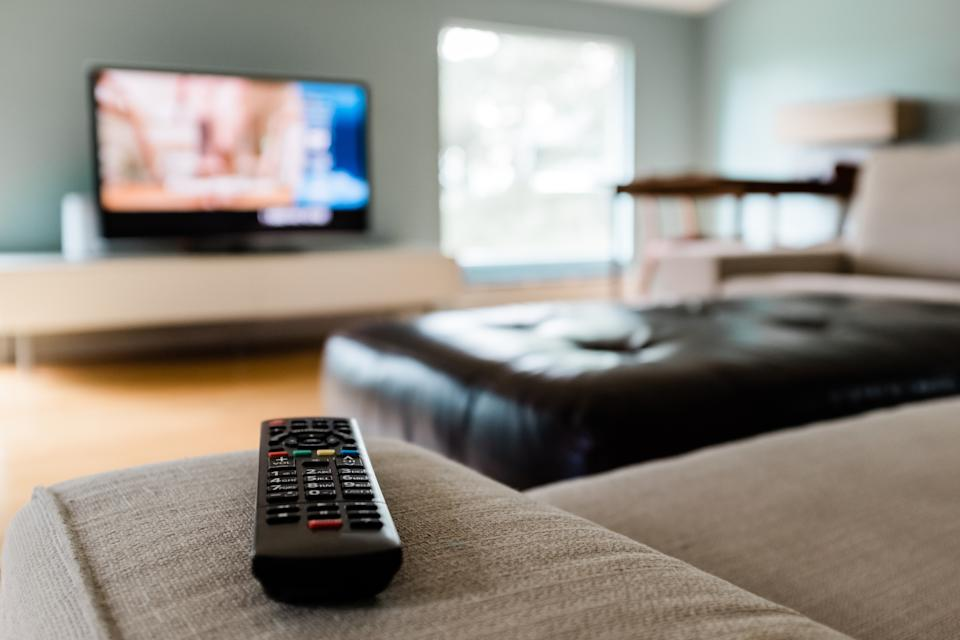 Close-up of a remote control sitting on a couch in an empty modern living room.