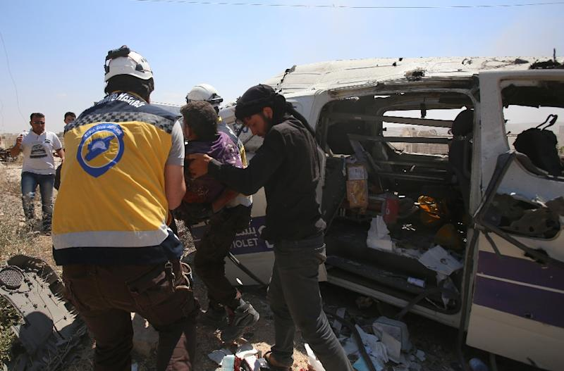 Syrian rescuers at the scene of an air strike that hit an ambulance in the town of Maaret al-Numan in northwest Syria on June 20