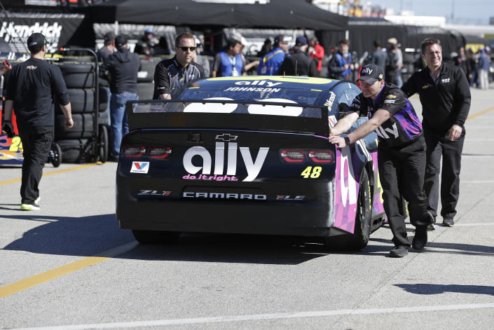 Crew members push Jimmie Johnson's car through the garage area during a NASCAR auto race practice at Daytona International Speedway, Saturday, Feb. 8, 2020, in Daytona Beach, Fla. (AP Photo/John Raoux)
