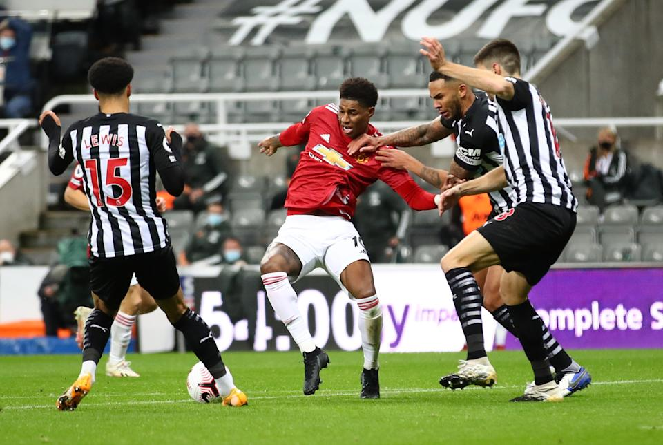 Manchester United's Marcus Rashford (centre) iis fouled in the penalty area by Newcastle defenders.