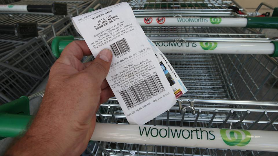 A Woolworths shopper holds a receipt in front of Woolworths trollies.