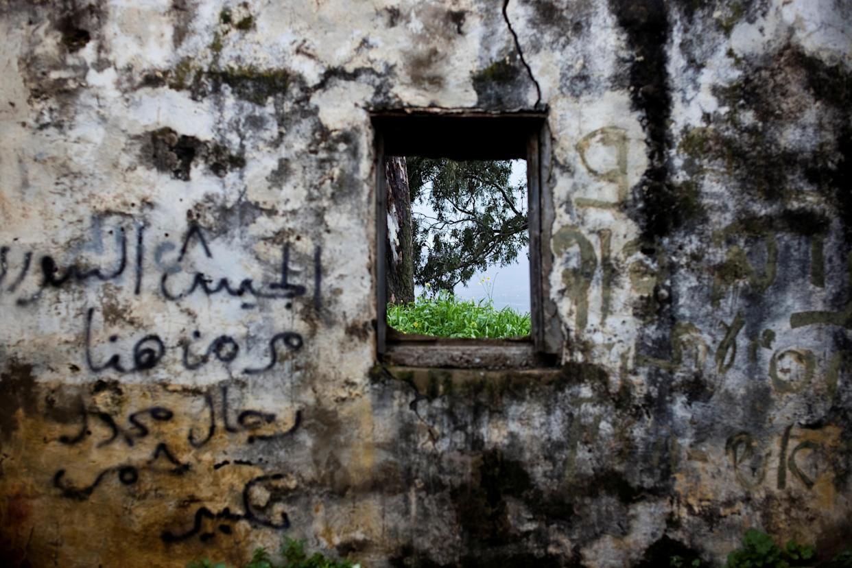 "The wall of a structure is seen in a former Syrian outpost in the Israeli-occupied Golan Heights, the territory that Israel captured from Syria in the 1967 Six Day War, Feb. 27, 2019. In stark contrast to the beauty of the surrounding countryside, it is now crumbling and covered in graffiti. One Arabic message reads: ""The Syrian army passed by here."" (Photo: Ronen Zvulun/Reuters)"