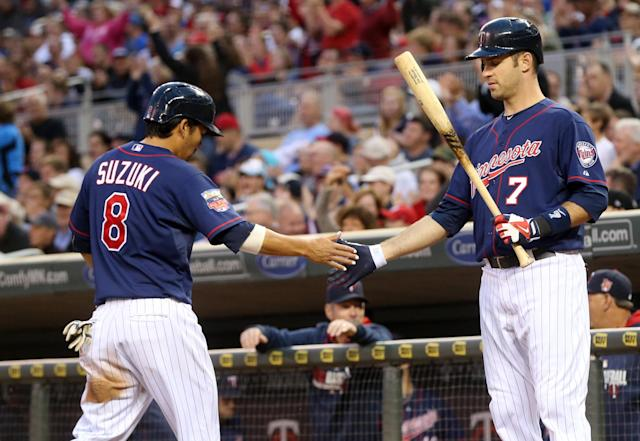 Minnesota Twins' Joe Mauer, right, congratulates Kurt Suzuki after he scored on a hit by Eduardo Nunez in the fourth inning of a baseball game, Tuesday, July 1, 2014, in Minneapolis. Mauer followed up with a two-run double. (AP Photo/Jim Mone)