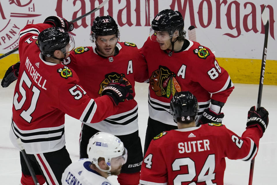 Chicago Blackhawks' Alex DeBrincat, second from left, celebrates with Ian Mitchell, left, Patrick Kane, right, and Pius Suter after scoring his second goal during the second period of an NHL hockey game against the Tampa Bay Lightning in Chicago, Friday, March 5, 2021. (AP Photo/Nam Y. Huh)