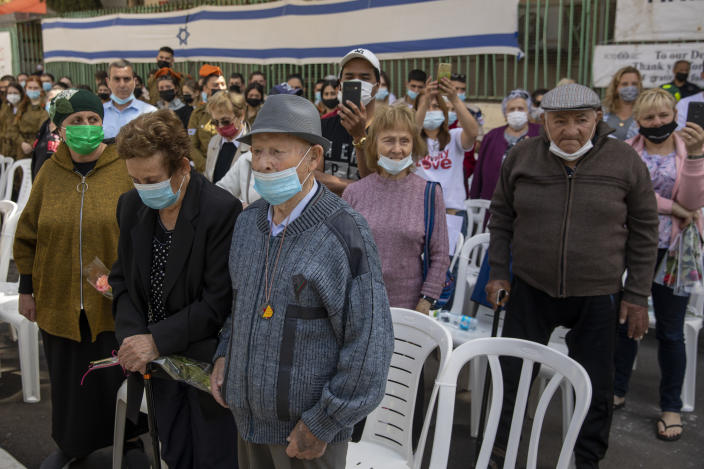 Holocaust survivors wearing face masks amid the coronavirus attend the yearly Holocaust Remembrance Day ceremony in Haifa, Israel, Thursday, April 8, 2021. (AP Photo/Ariel Schalit)