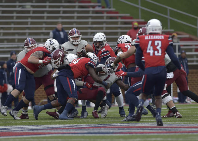 Liberty players take down New Mexico State's Jason Huntley during an NCAA college football game in Lynchburg, Va., on Saturday, Nov. 30, 2019. (Taylor Irby/ News & Advance via AP)